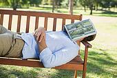 Man sleeping on park bench with new