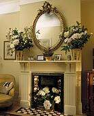 Stock Photograph of Clock and lighted candles on mantelpiece above ...